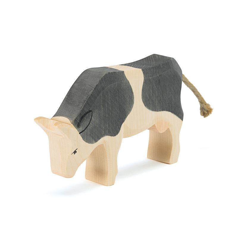 Black and White Cow Eating Wooden Toy