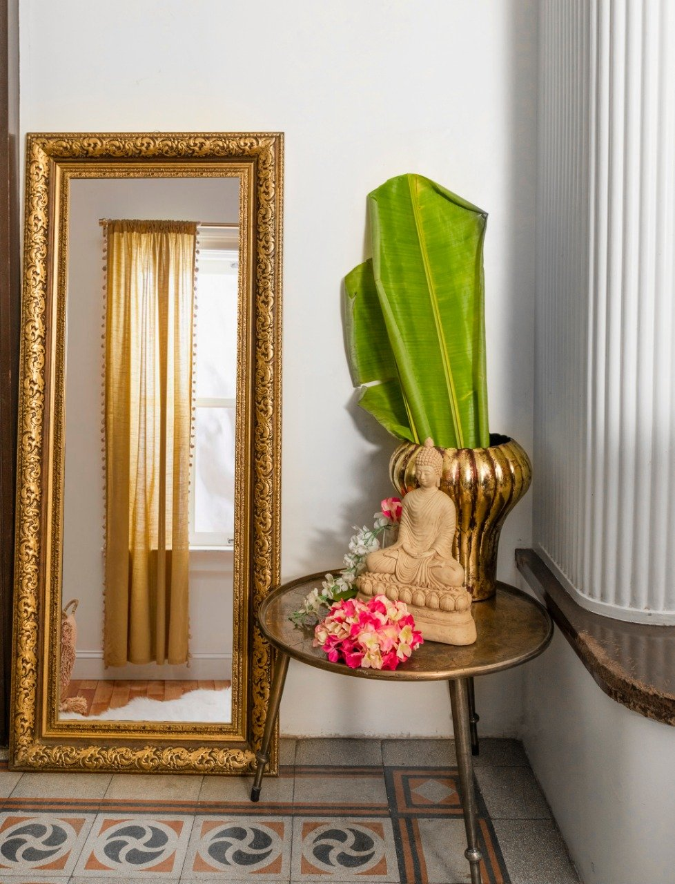 A Wall Mirror with a Metal Frame with details depicting antique carvings in an antique gold finish at an amazing price!