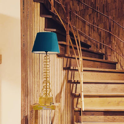 A gold stem lamp with a snake like detail paired with a teal lamp shade.