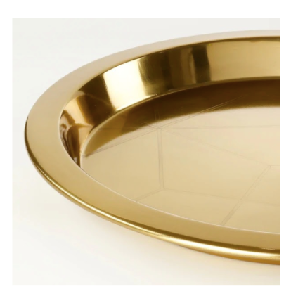 A big, round gold tray, made of metal with a geometric pattern within.