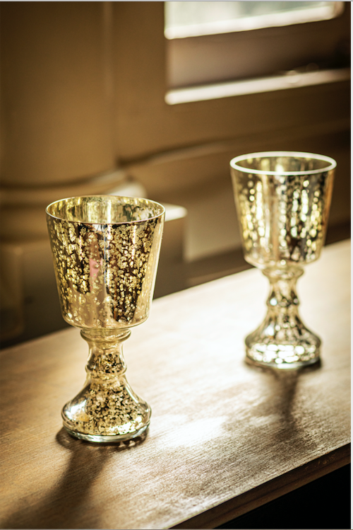 A glass chalice candle holder along with gold & silver leaf detailing