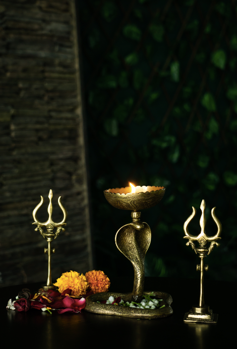 A brass snake diya with an antique gold finish