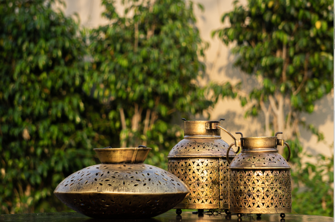 an antique gold jaali candle stand with provisions to hold tea light candles