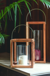 Structural wooden lanterns made of mango wood with a metal handle on top and a cylindrical glass candle holder within