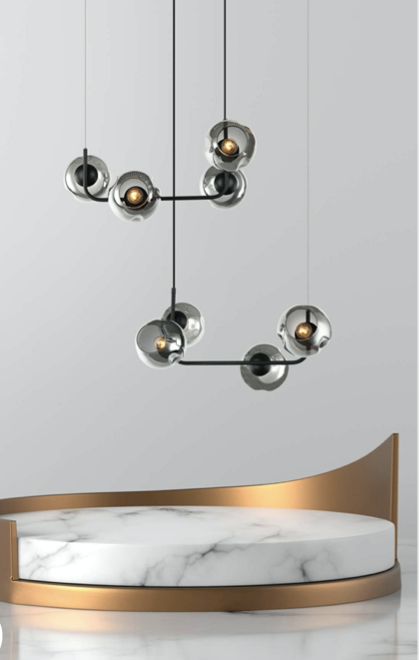 an ash gray metal and glass chandelier suspended from the ceiling with grey goblet glass domes surrounding the bulb ports.