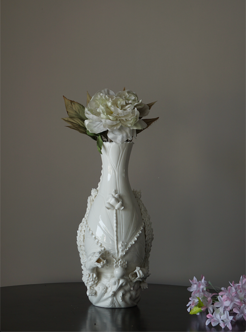 A white porcelain flower vase with details depicting floral designs and dragons.