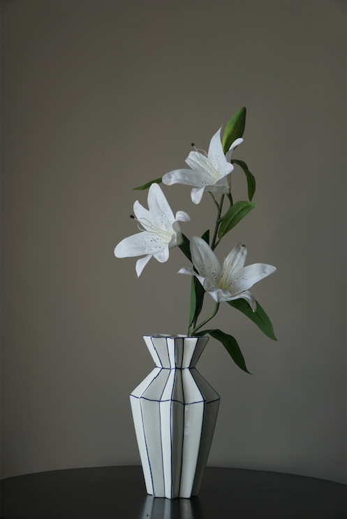 A symmetrically pleasing white porcelain flower vase with precise symmetrical corners highlighted in Royal Blue.