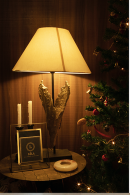 A Brass lamp with a textured gold finish and a black stem