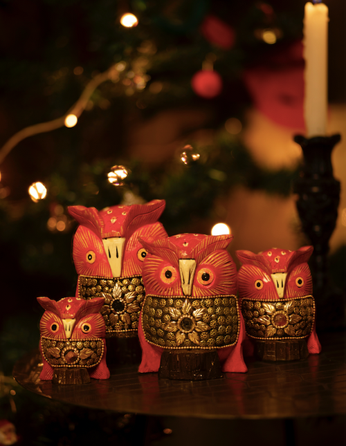 A collection of four red wooden owls with hand painted and hand carved details.