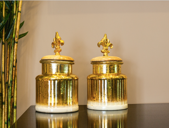 A Pair of two gold glass jars with covered with metal lids.