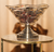 A glass decorative bowl made with crinkled glass supported by a metal stand.