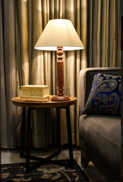 A wooden lamp made with mango wood, carved with elegant detailing along with a beige lamp shade.
