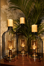 Load image into Gallery viewer, A Set of 3, are made of metal, in a glossy black finish supported by a metal base underneath, that comes in a chrome gold finish. The Murk Metal Lanterns are partially open on one end to keep your choice of candles within the glass candle holder that is supported by another metal stand within, on which it is mounted upon.