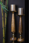 A pair of candle stands, moulded out of timber wood, with gold accents on the top and the stem of the stands.