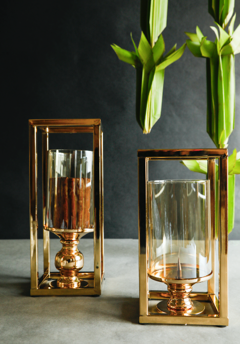 A brass candle stand set enclosing glass cases for the candles along with a brass stand adorned with a gold finish making this suitable for all interior styles.