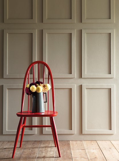 Red Chair In Front Of Beige Panel Wall