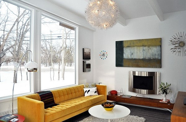 Yellow Sofa In Modern White Living Room, Snowy Woods Visible Outside Of The Window