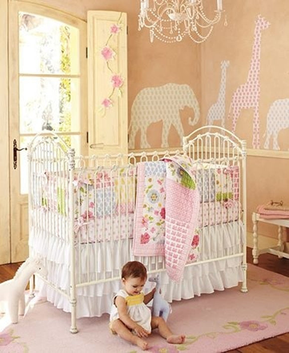 Animal cutouts using different patterned paper, stuck to a nursery wall, with bay playing on the floor
