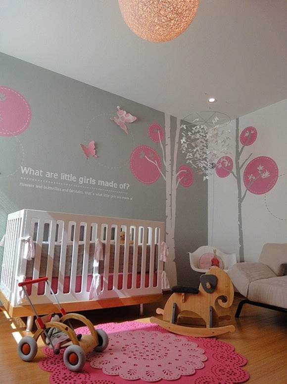 Girls grey and pink nursery with white and grey trees on the walls and a pink doily like rug