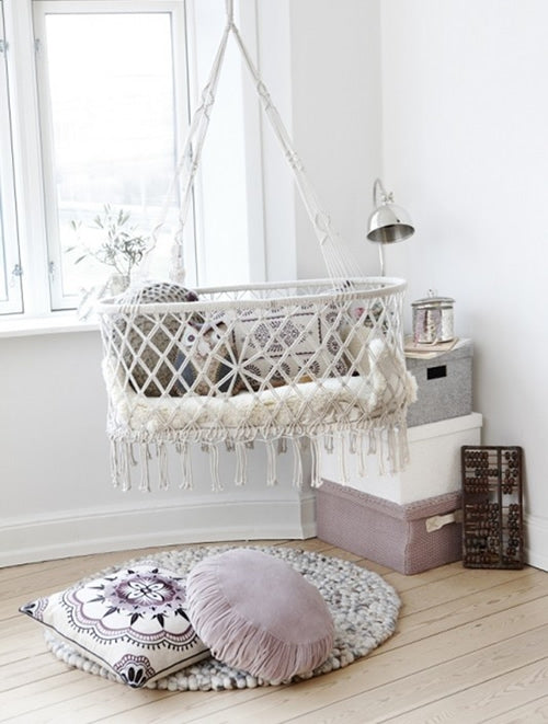 Minimalist white nursery with macrame like hanging cot