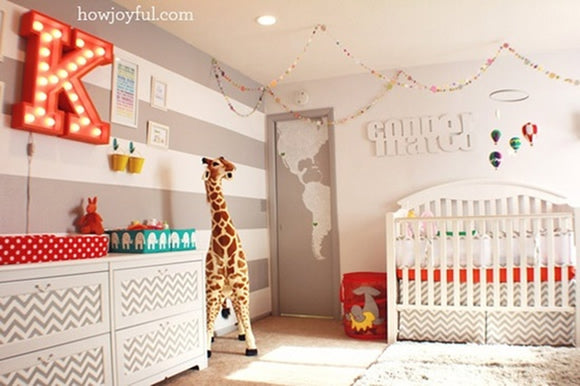 Cream and beige striped nursery with America map on the door, large letter K in red on the wall and large stuffed and free standing Giraffe teddy
