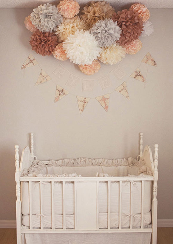 Creamy beige nursery with autumnal pom-poms above a cot