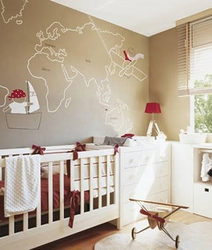 Beige nursery with a white outline of the world map on the wall, plus aeroplane and boat