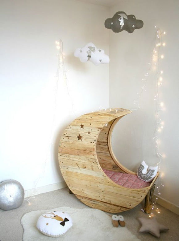 Wooden Moon cot with fairy lights as stars and paper cut out clouds hanging from the ceiling