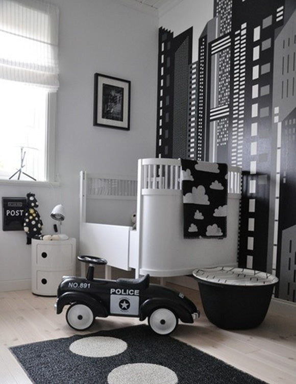Black and white city themed nursery, with skyscraper wall art and a play police car on the floor