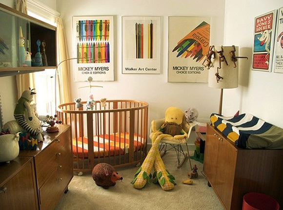 Eclectic cream nursery with wooden storage units and creative artwork on the walls
