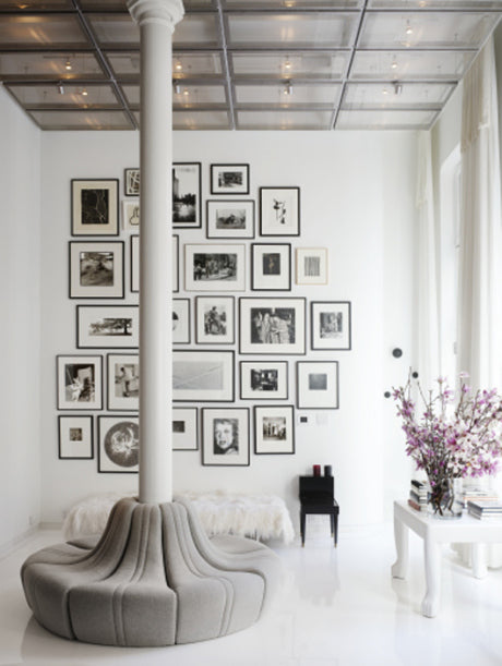 Ceiling support column with a surrounding seat bench and lots of photo frames on the walls