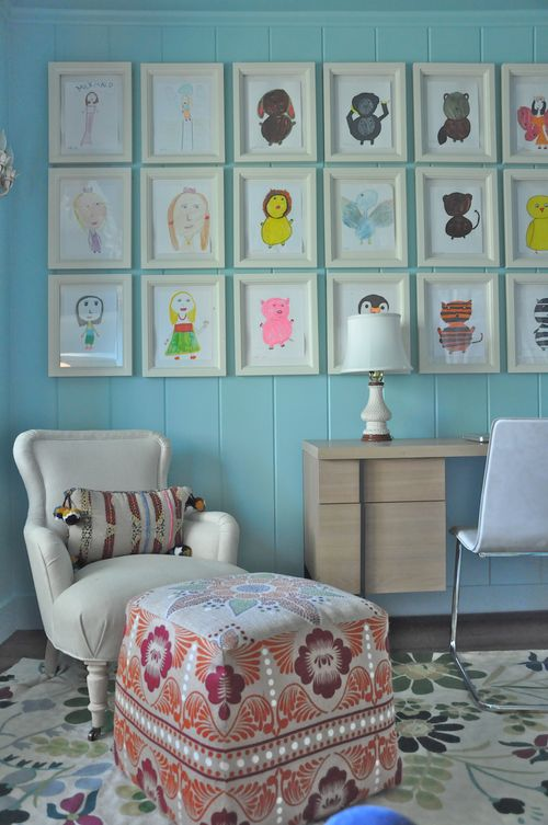 Light blue panel walls, white arm chair and childrens photos on the wall
