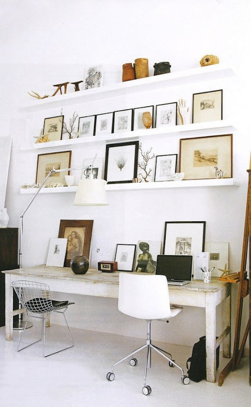 White shelves ona white wall filled with picture frames, above a Scandinavian style desk