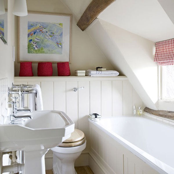 Cream bathroom interior with sloping roof and red accent colours