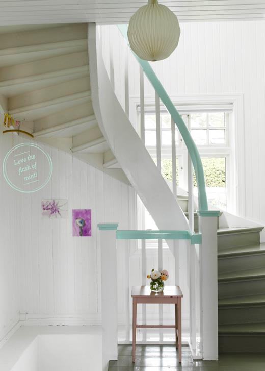 Curving staircase in a beach hut style home, with white wooden panel walls and duck egg blue banister