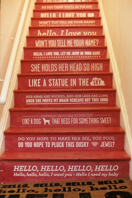 Red wooden staircase with white writing on each step, that are the lyrics to the song I love you by The Doors