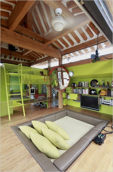 High ceiling green den room with exposed ceiling beams