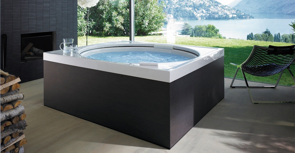 Large square hottub style bath in a room with floor to ceiling windows, with a view of the river and hills