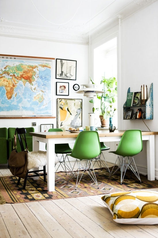 Scandinavian dining table and green plastic chairs with world map in the background