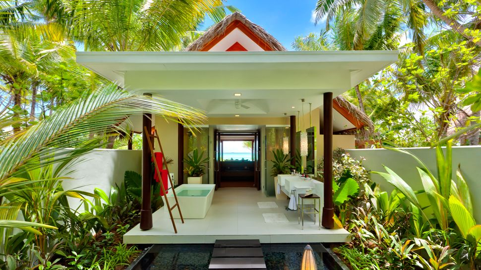 Luxury villa with outdoor bathtub and sinks under a white veranda, with lots of plants and greenery