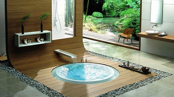 Small round bathtub on a wooden floor that seamlessly slopes upto wooden matching wall panels
