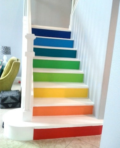 A white staircase with the front of each step in a different colour like a rainbow