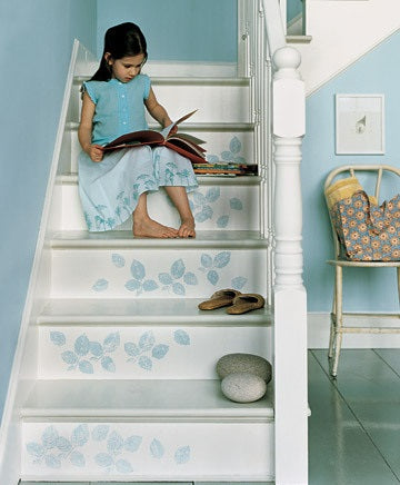 A young girl siting on a white staircase, with a light blue floral pattern on the front of each step