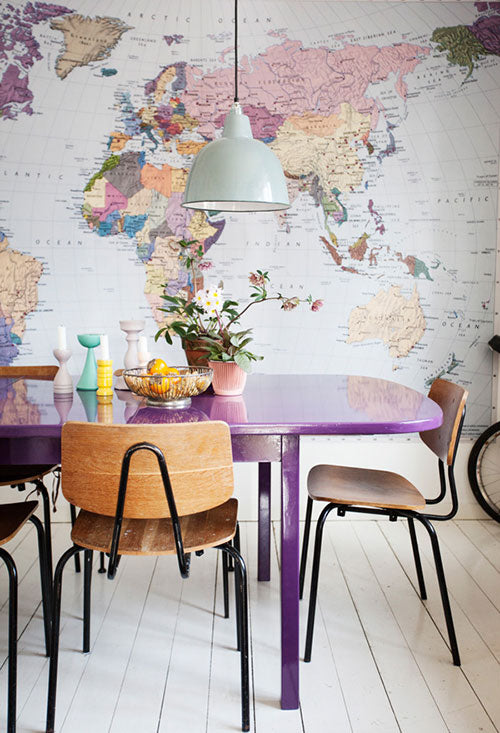 Coloured world map, with purple dining table in the foreground