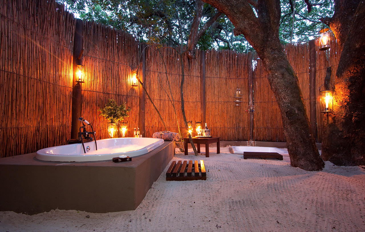 Bamboo screens providing privacy for an outdoor bathtub with mood lighting provided by lanterns