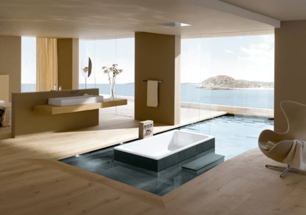 Luxury bathroom with bath tub embedded in an infinity pool overlooking the sea