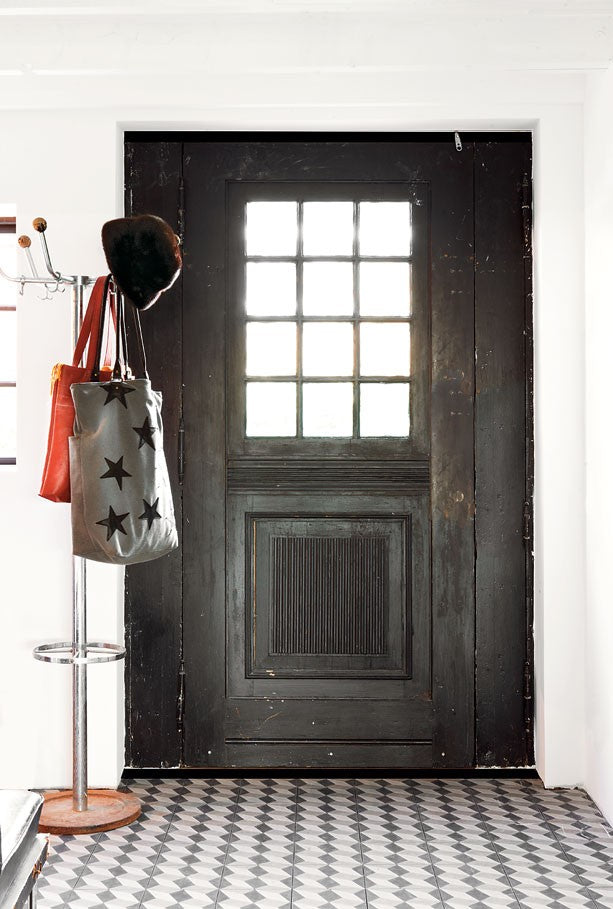 Rustic black front door, with glass grid centre allowing light into a white hallway