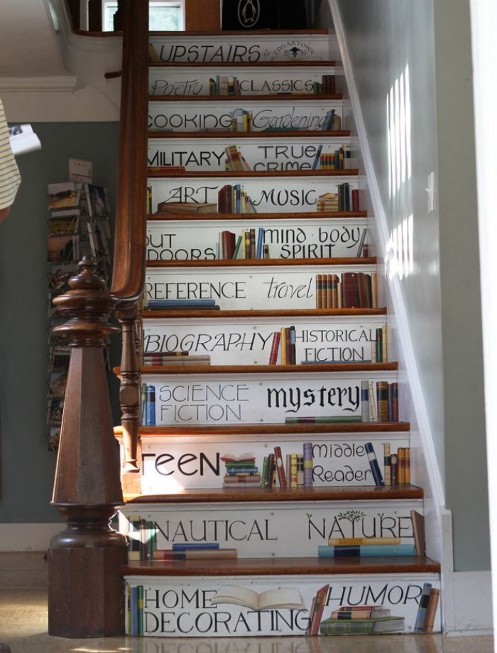 Traditional wooden staircase with white decals on each step depicting books from different genres