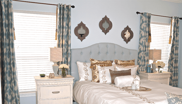Cream bedroom with light blue and cream eyelet curtains either side of the bed
