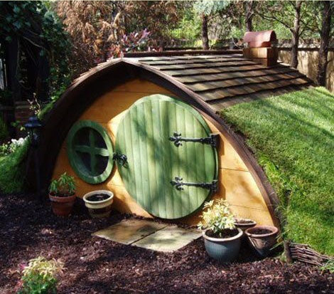 Hobbit style semi circle playhouse with grass on the roof